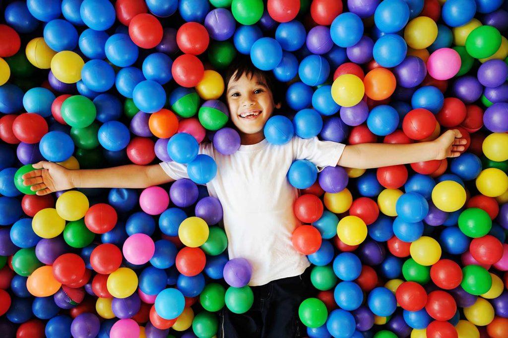 Παιδί χαρούμενο βουτηγμένο μέσα σε μπάλες